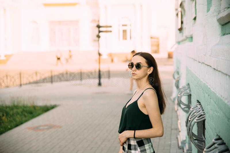Sexy girl in a T-shirt and short shorts near the building.  stock photo