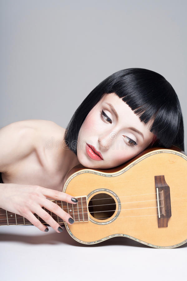 Girl with ukulele guitar.music. Concept. beautiful young woman with bob haircut stock photo