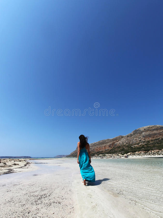 Girl walking on the beach in a turquoise dress. Beautiful woman in turquoise long dress walking on the beach of Balos lagoon Crete Greece royalty free stock photography