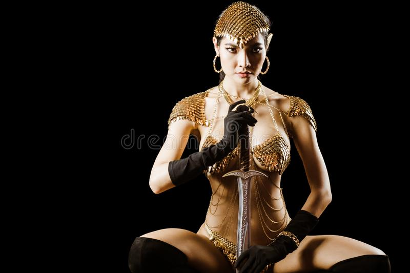 Sexy girl wearing golden queen of warrior armor fancy dress looks elegant and luxury for advertising fashion model stock photo