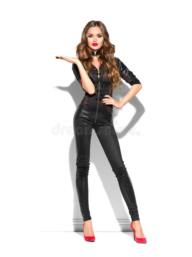 Sexy Girl wearing leather costume and high heels, with long curly hair pointing hand, showing product. Sales, Party, Celebrating. Beauty Woman isolated on royalty free stock image