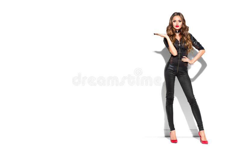 Sexy Girl wearing leather costume and high heels, with long curly hair pointing hand, showing product. Sales, Party, Celebrating. Beauty Woman  on white stock image
