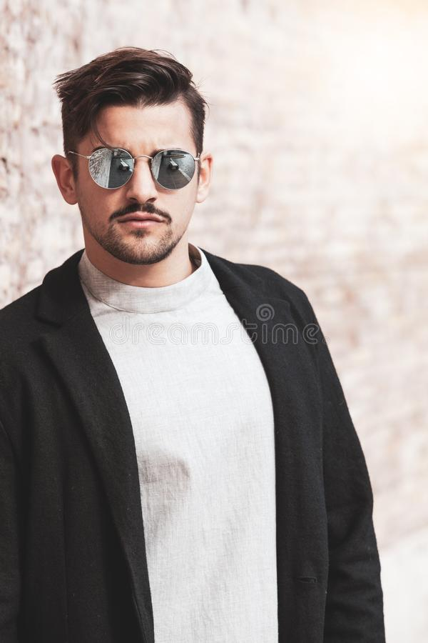 Sexy gorgeous stylish man. Sunglasses. City style. A beautiful and charming man with sunglasses outdoors. royalty free stock image