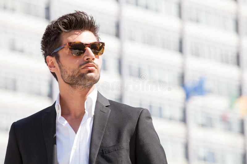 Gorgeous stylish man. Sunglasses. City style. A beautiful and charming man with sunglasses outdoors. Stubble and blacks hair. Intense light. White shirt and stock image
