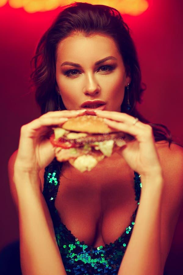 Gorgeous woman eating hamburger in night club royalty free stock image