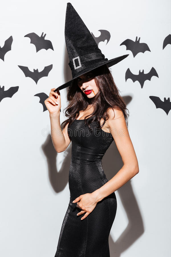 Gothic young woman in witch halloween costume with hat. Gothic young woman in black witch halloween costume with hat posing over white background stock images