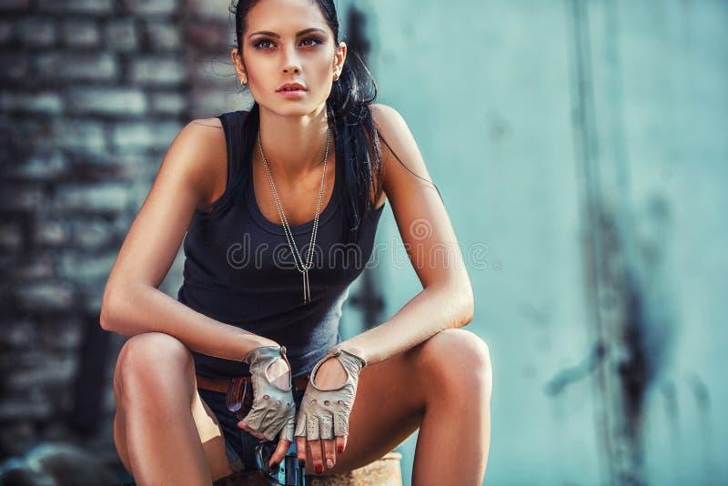 Sexy grobe Frau, die Pistole sitzt und hält lizenzfreies stockbild
