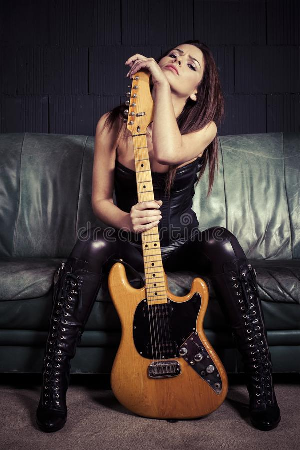 Sexy guitar player sitting on couch royalty free stock image
