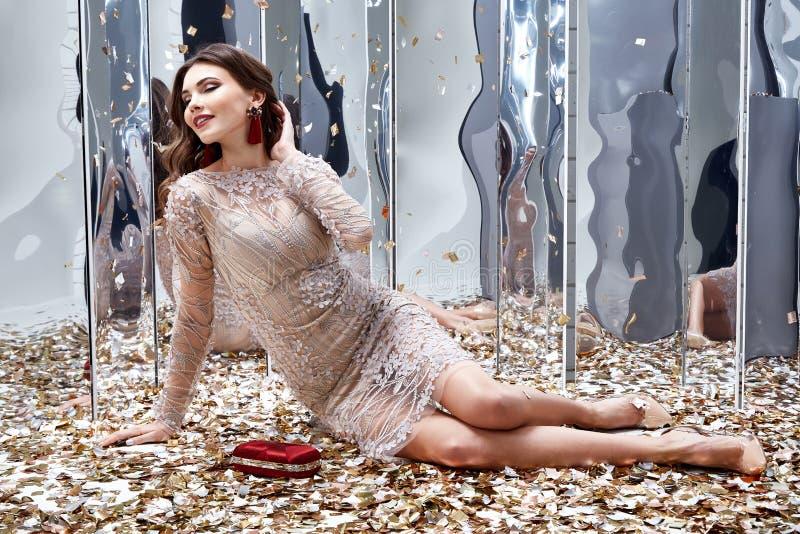 Sexy hübsche Frau sitzen Boden mit Los goldenem Paillettezauber f lizenzfreies stockfoto