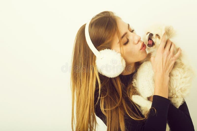 Sexy hübsches Mädchen, das kleinen pomeranian Hund in den Ohrenschützern küsst stockfotos