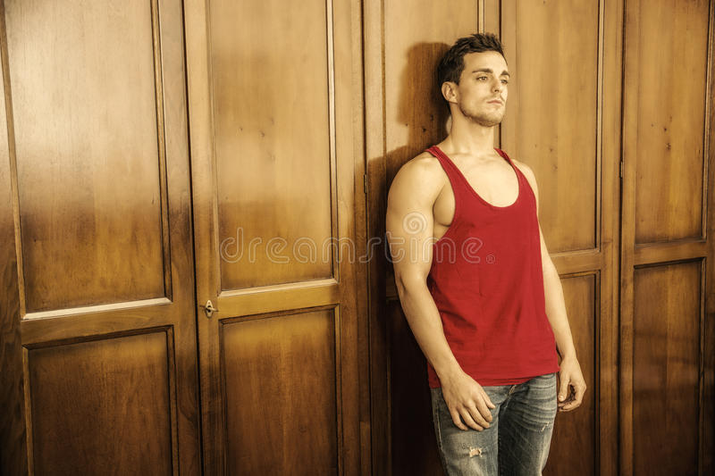 Handsome young man in front of wardrobe. Handsome young man standing in red tank-top in front of wood closet doors stock images