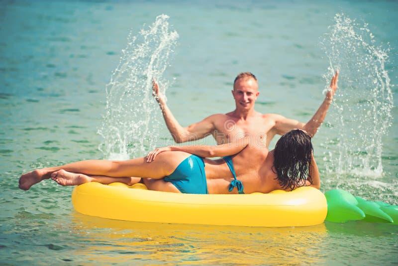 Sexy happy couple on Caribbean sea. Pineapple inflatable mattress, activity joy. Maldives or Miami beach water. Couple. In love sunbath on beach on air mattress stock photo