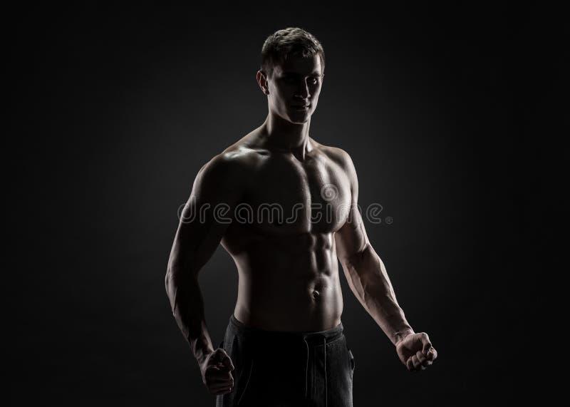 Sexy hemdlose Bodybuilderaufstellung, Kamera auf schwarzem Hintergrund betrachtend lizenzfreies stockbild