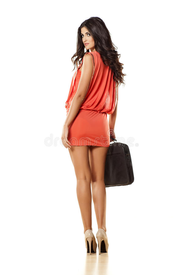 In her dress. Rear view of an attractive girl in short orange dress and laptop bag on white background royalty free stock photos