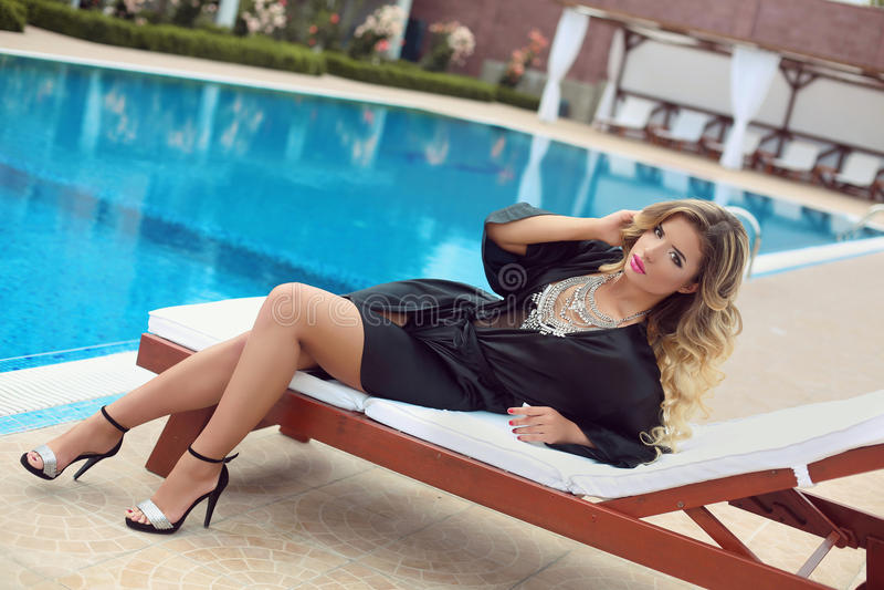Sexy het meisjesmodel dat van de luxetoevlucht in manierkleren op bea ontspant stock fotografie