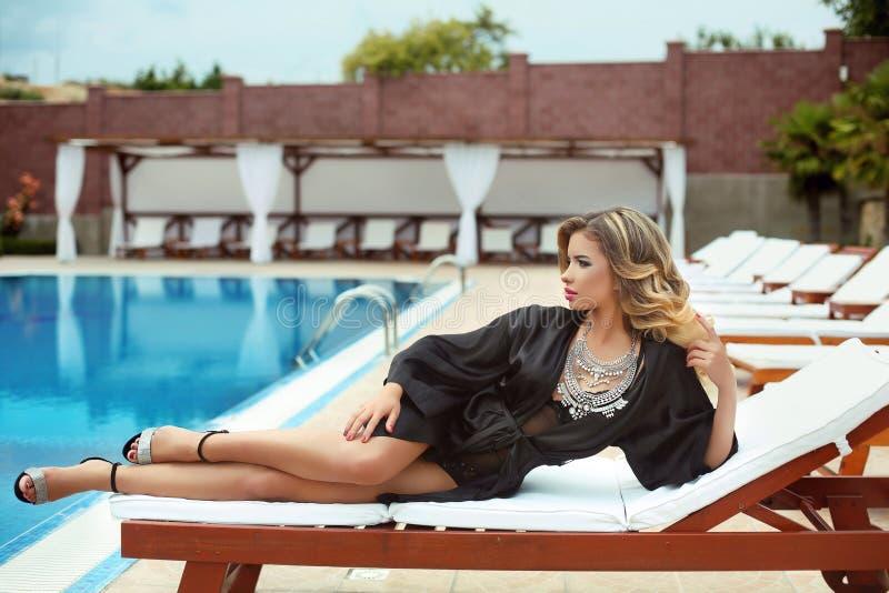 Sexy het meisjesmodel dat van de luxetoevlucht in manierkleren op bea ontspant royalty-vrije stock foto's