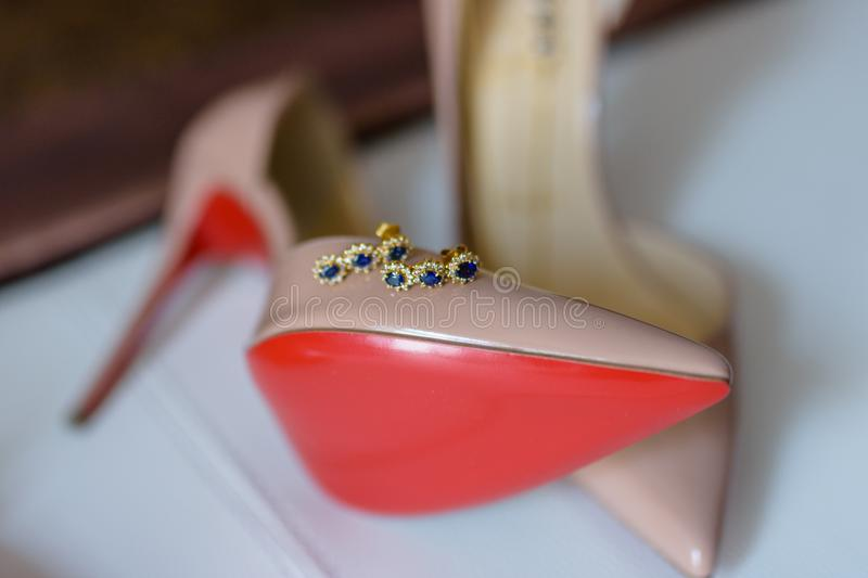 High heel shoes with red bottom. High heel shoes with grandma`s earrings on them on white background. Shallow DOF, foreground out of focus stock photos