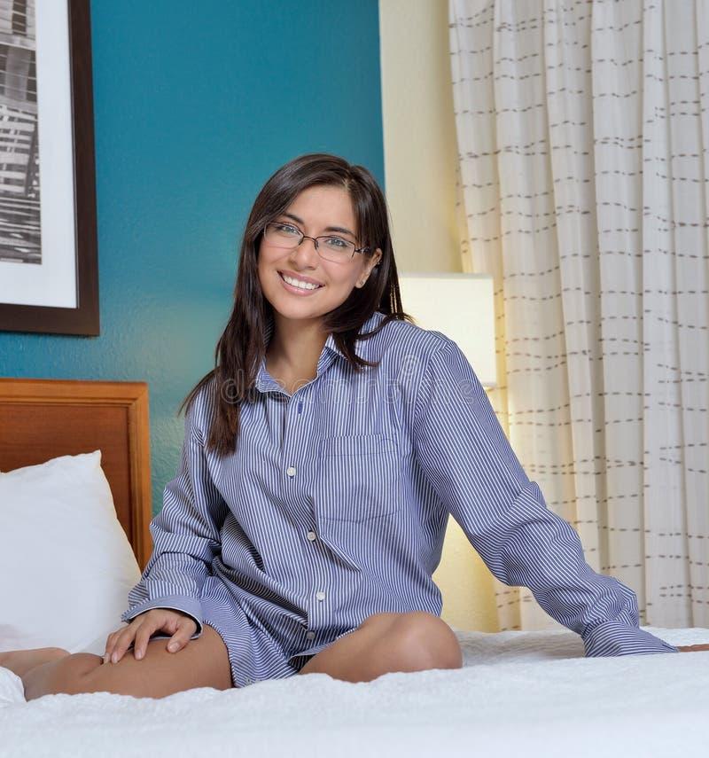 Sexy hispanische Frau, die in das Hemd der Bettmänner legt stockfotos