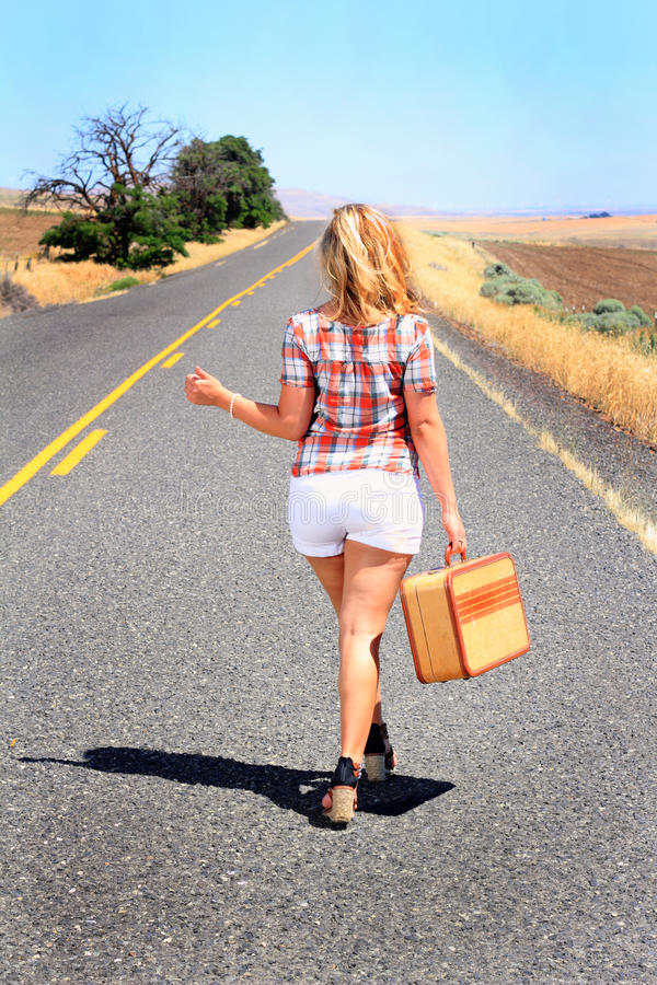 Hitch Hiker Thumbing It. A blonde beauty wearing shorts is hitching a ride with a suitcase on a desolate country road royalty free stock images
