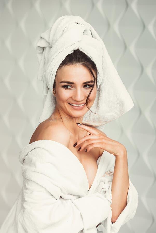 Sexy jong meisje met donker haar, grote ogen en donkere wenkbrauwen die de witte handdoek van de badrobe whith op haar hoofd drag stock afbeeldingen