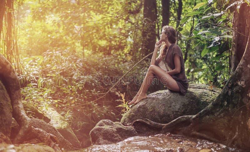Sexy jonge dame die in het tropische bos rusten stock afbeeldingen