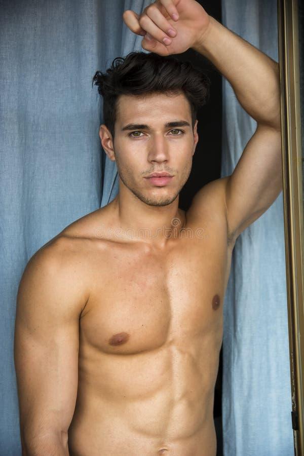 Sexy jonge mens die zich shirtless door gordijnen bevinden stock foto's
