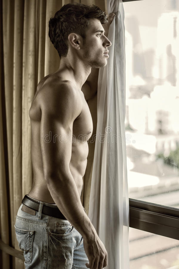 Sexy jonge mens die zich shirtless door gordijnen bevinden royalty-vrije stock afbeeldingen