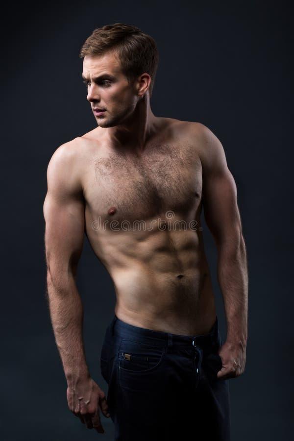 Sexy jonge mens met een naakt torso op een donkere achtergrond stock afbeeldingen