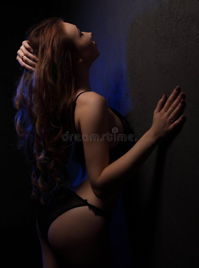 Sexy jonge mooie vrouw met krullen in sensuele zwarte die lingerie, met blauw in studio dichtbij muur, ezelsschouder en haar in l royalty-vrije stock foto's
