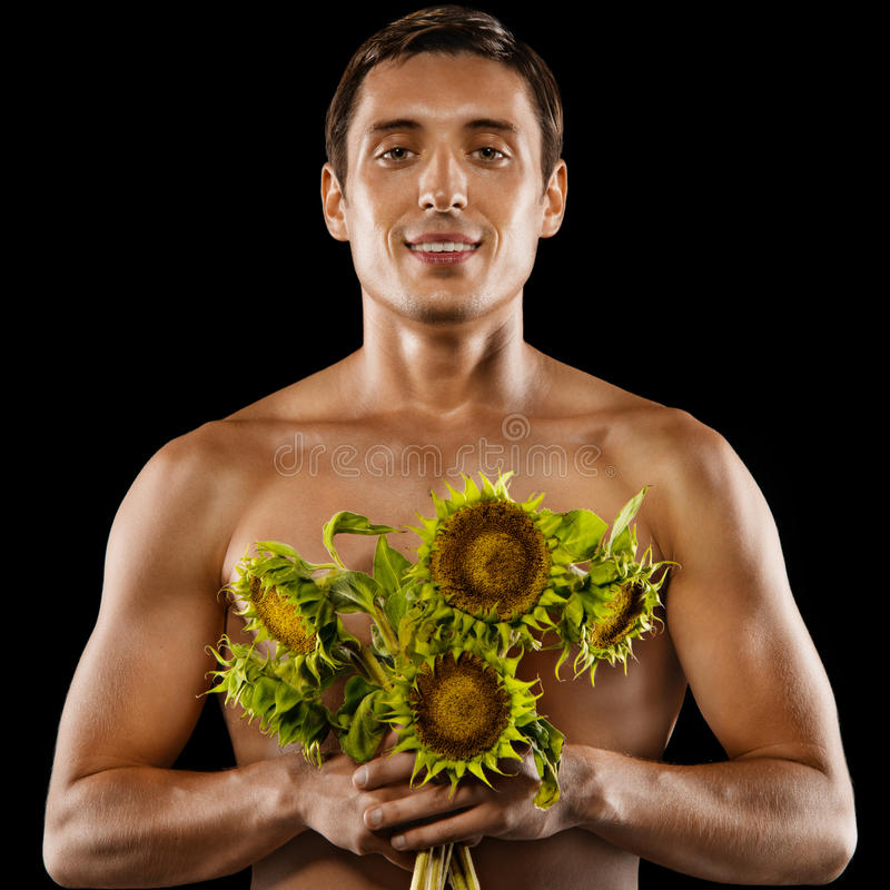 Sexy jonge spiermens met een boeket van bloemen stock afbeeldingen