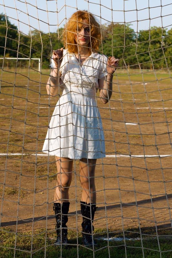 Sexy jonge vrouw bij voetbalpoorten stock fotografie
