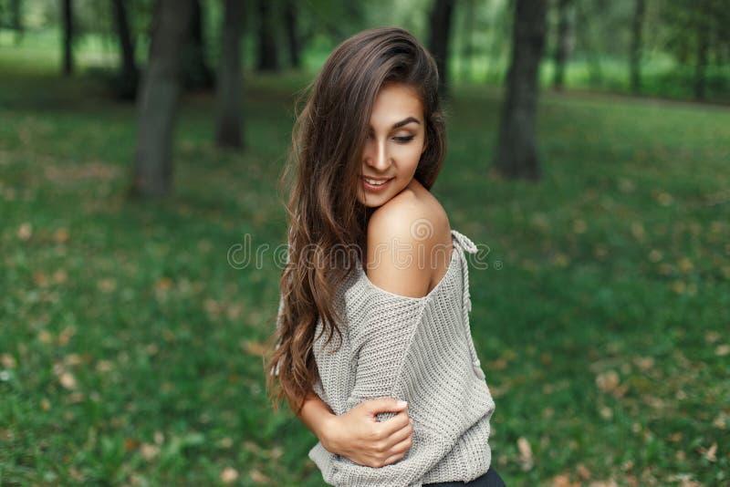 Sexy jonge vrouw die in een uitstekende grijze sweater dichtbij glimlachen royalty-vrije stock afbeeldingen