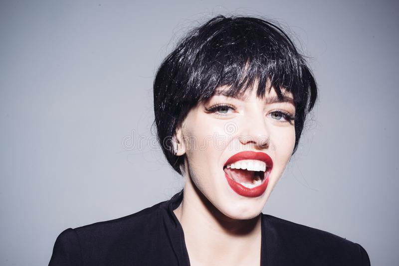 Sexy jonge vrouw die haar rode lippen likken Sensueel wijfje die zwarte pruik en overmaats die jasje dragen op grijze achtergrond stock fotografie