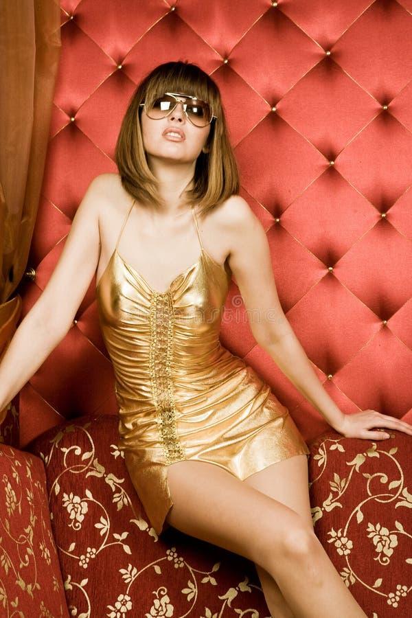 Sexy jonge vrouw in gouden kleding stock afbeeldingen