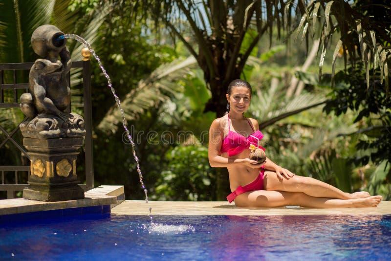 Sexy jonge vrouw in het roze zwempak ontspannen bij pool stock afbeelding