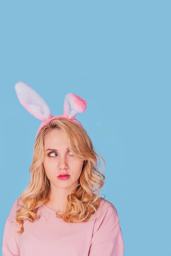 Sexy jonge Vrouw met Bunny Ears Glimlachend die Pasen-Meisje op wit wordt geïsoleerd Het kijken op Pasen-Meisje op blauw wordt ge royalty-vrije stock fotografie