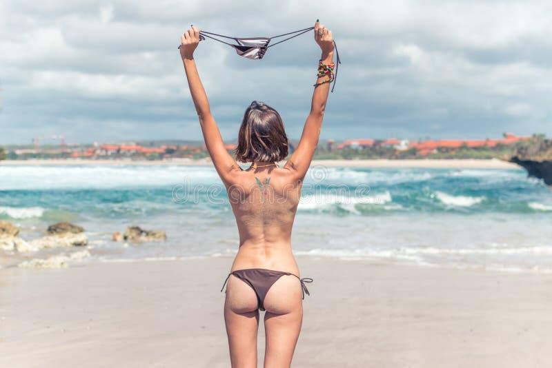 Sexy jonge vrouw zonder bustehouder op het tropische strand van het eiland van Bali De vrijheidsconcept van het bikinimeisje indo royalty-vrije stock afbeelding