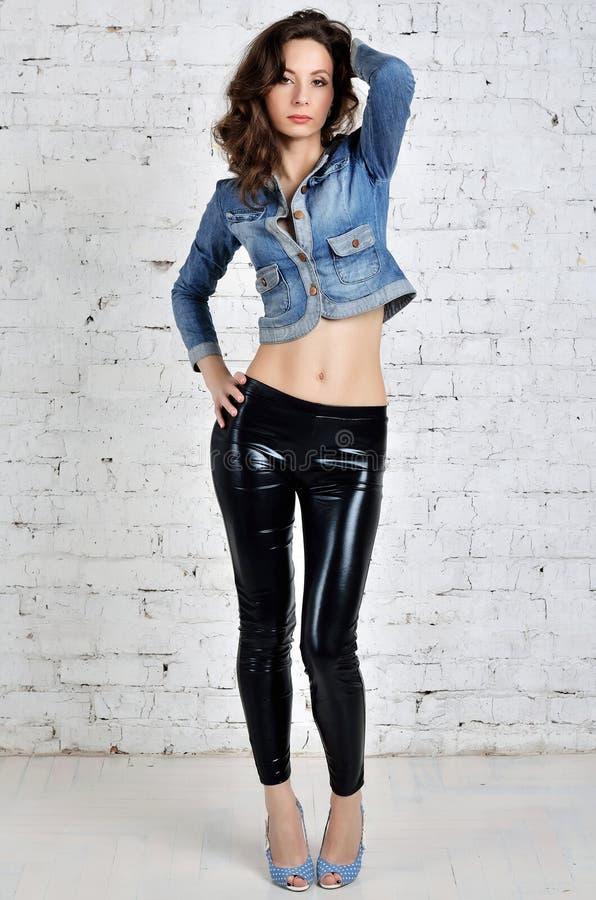 Sexy jonge vrouw in zwarte broeken en een denimjasje stock foto's