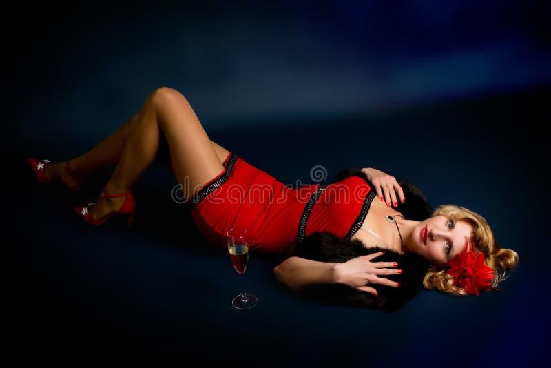 Sexy junge blonde Frau in einem roten Kleid auf einem Schwarzen stockfotografie