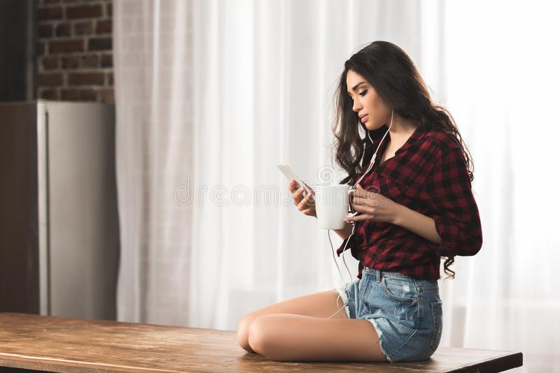 sexy junge Frau in den Kopfhörern unter Verwendung des Smartphone beim Trinken des Kaffees stockfoto