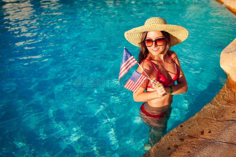 Sexy junge Frau, die USA-Flagge im Swimmingpool h?lt Feiern des Unabh?ngigkeitstags von Amerika stockfoto