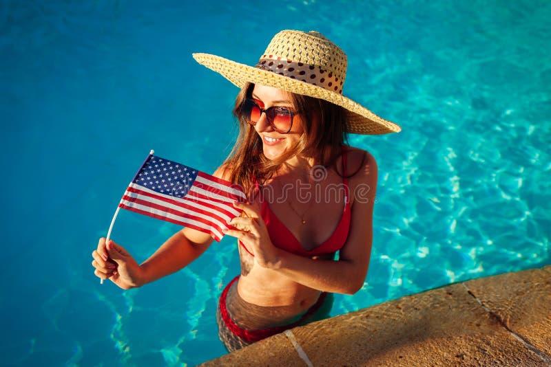 Sexy junge Frau, die USA-Flagge im Swimmingpool h?lt Feiern des Unabh?ngigkeitstags von Amerika stockfotografie