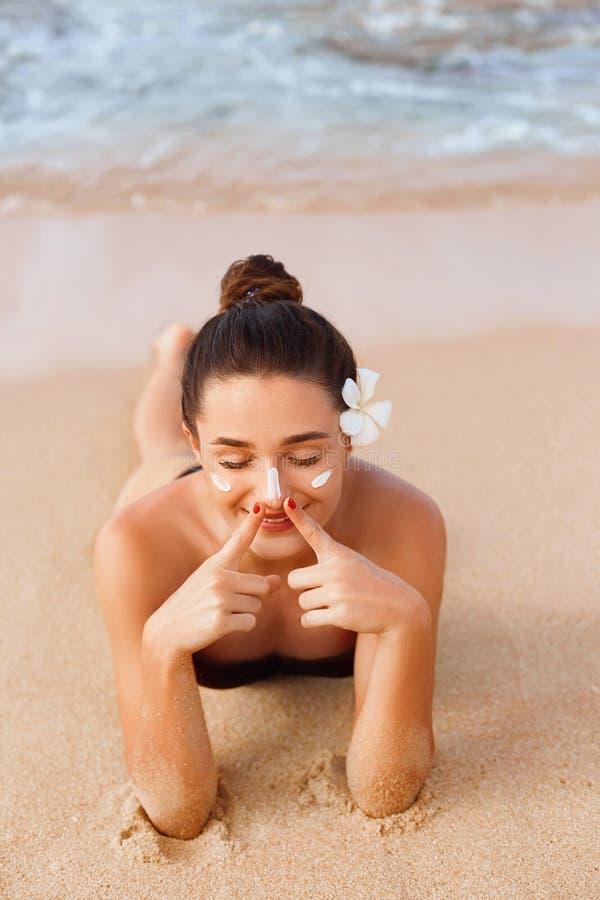 Sexy junge Frau im Bikini, der Flaschen Lichtschutz in ihren H?nden h?lt Skincare Eine schöne weibliche zutreffende Sun-Creme Unt stockfotografie