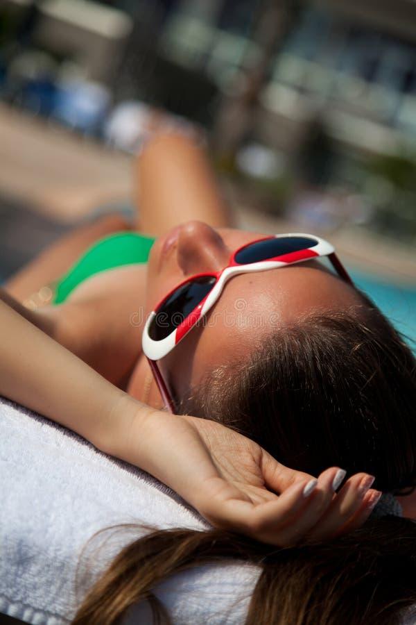 Sexy junge Frau im Bikini ein Sonnenbad nehmend stockfotos