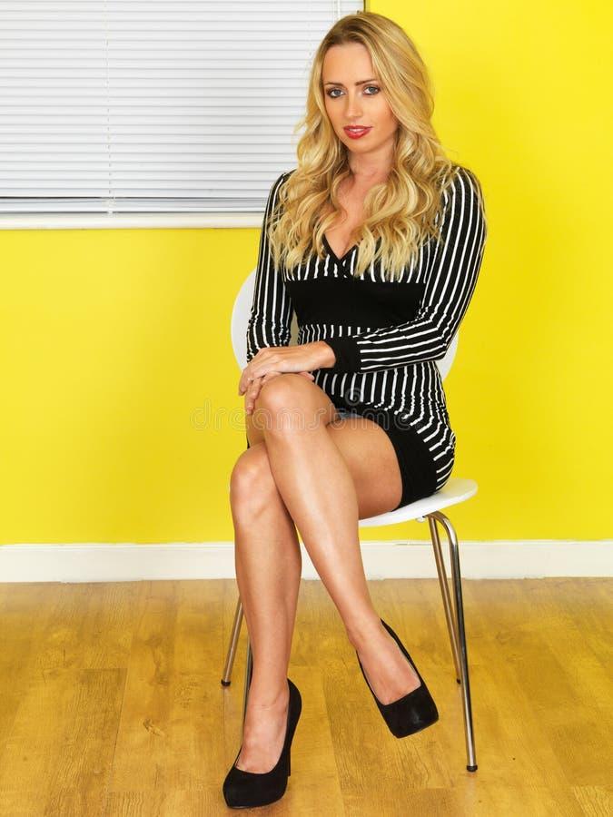 Sexy junge Geschäftsfrau in einem kurzen Mini-Kleid lizenzfreie stockfotografie