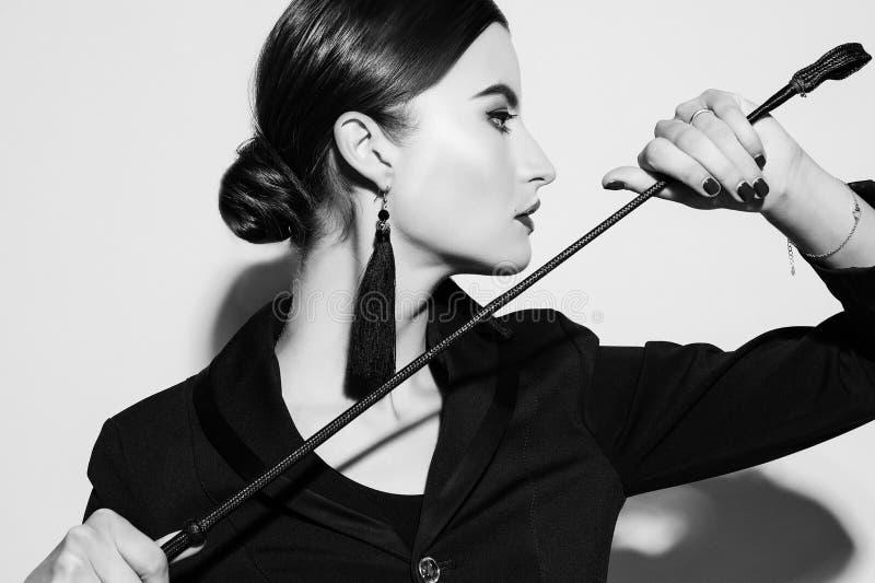 Sexy junge schöne dominierende Dame, die in der schwarzen Ausstattung aufwirft lizenzfreie stockfotografie