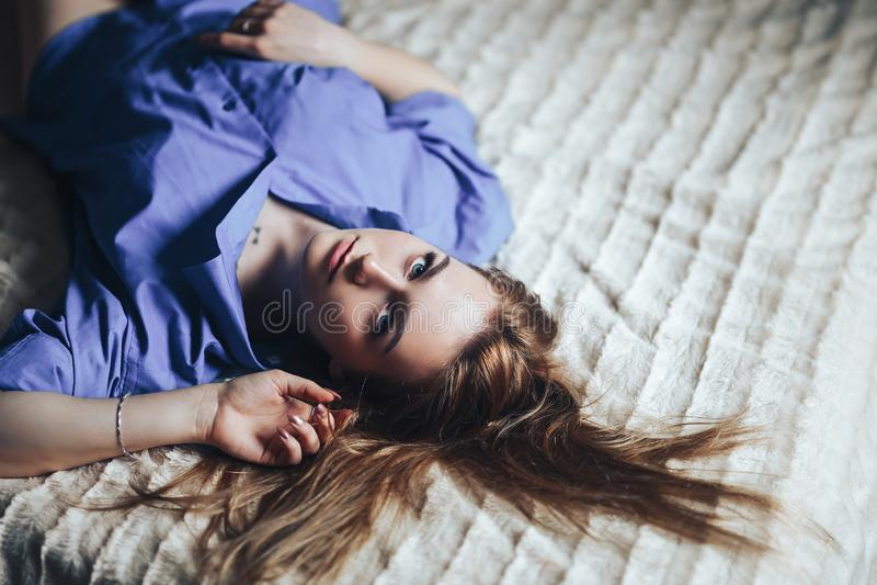 Sexy junge Schönheit mit blauem großem Augen lond Haar, das zu Hause auf Bett im blauen Hemd liegt stockbilder