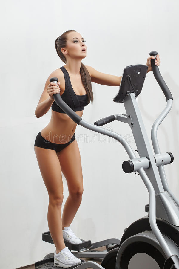 Sexy junge Sportlerin, die auf Simulator trainiert stockfoto