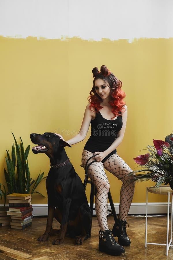 Sexy junge vorbildliche Frau mit dem roten Haar und mit perfektem Körper in den schwarzen stilvollen Bodysuits und in der Maschen stockfoto