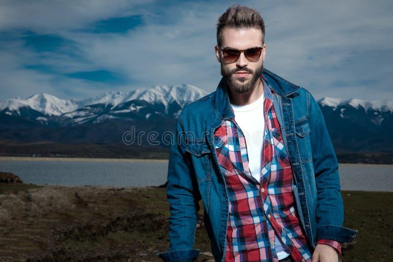 Sexy junger Mann in der Denimkleidung und -Sonnenbrille, die äußer steht stockfotografie